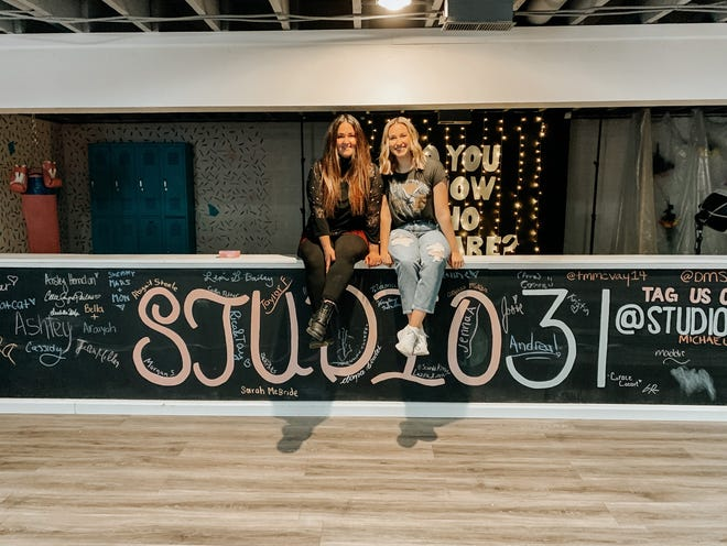 Allie Sayre-Phillis, left, and Aisley Herndon sit atop their chalkboard wall Thursday in The Babe Cave at Studio 31 Akron.