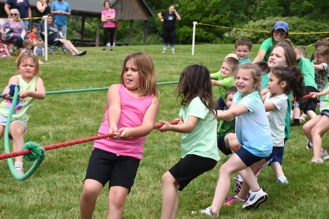 A young girl works hard while competing in the tug of war during the recent West Branch Early Learning Center field day. The kindergartner was at the front of the line on her group's rope.