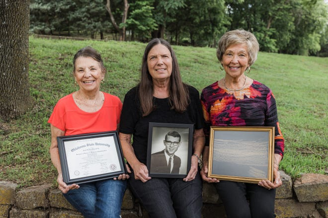 Sister Janice Banks, widow Sue Reynolds and sister Claudean Stotts hold J.D. Starrett's OSU diploma, portrait and a rubbing from the Vietnam War Memorial.