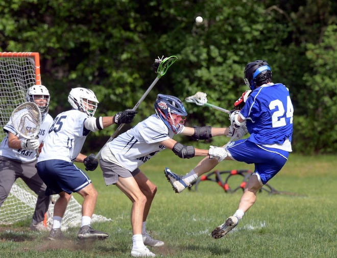 Jack DiFalco-Wheeler of  Falmouth Academy fires a shot on the Sturgis goal as Michael Bound pushes him off.