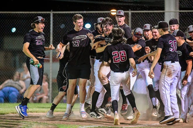The Chillicothe Mudcats summer baseball team joyfully celebrates as it surrounds teammate Tanner Sears (behind No. 28 Petey Taylor) following his ninth-inning walkoff home run with two outs that beat the Sedalia Bombers 10-9 at Trenton's Burleigh Grimes Field Wednesday.