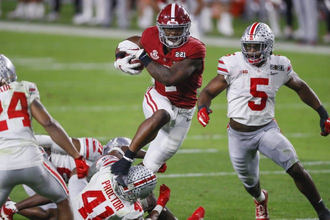 Alabama running back Brian Robinson Jr. jumps over Ohio State safety Josh Proctor (41) and linebacker Baron Browning (5) during the College Football Playoff championship.