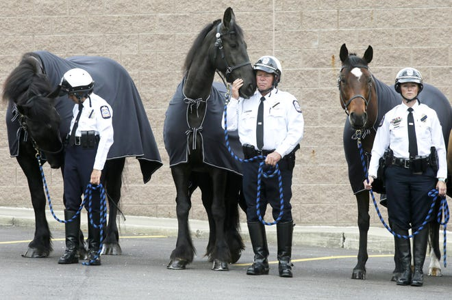 Members of the Columbus Division of Police's mounted unit stand Thursday during a memorial for Liberty, a 16-year-old Belgian horse, at the department's paddocks on Columbus' West Side. Liberty died on May 24th after battling an illness. Liberty was recently retired Sgt. Bob Forsythe's mount since she joined the unit in 2015.