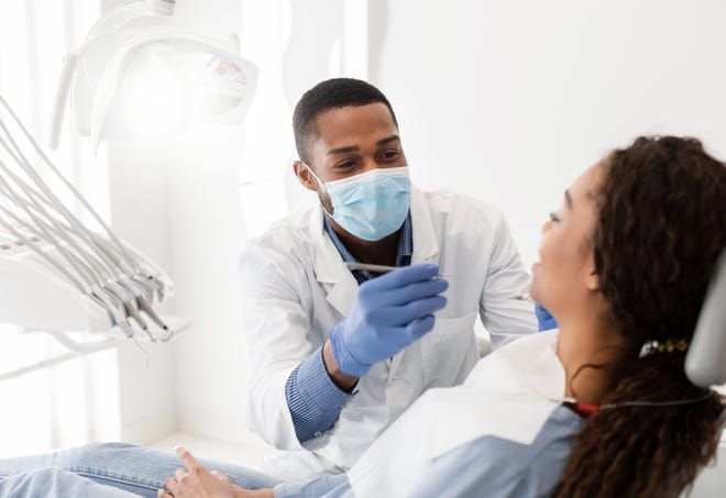 A dentists performs a dental treatment in a modern clinic.