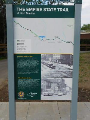 Dieses Schild zeigt eine Karte des Erie Canal Trail und historische Fotos von Ilion, die sich entlang des Erie Canal Trail östlich von Ilion Marina befinden.  Der Erie Canal Trail ist Teil des 750 Meilen langen Empire State Trail, der von New York City durch das Hudson River Valley, westlich entlang des Erie Canal nach Buffalo und nördlich nach Champlain Valley und den Adirondacks führt.