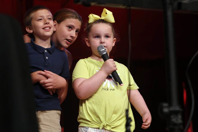 """Mikayla Donlan, 13, center, accompanies her brother, Terren, 9 and Onna Pappalardo, 5, Thursday as they sing """"Let It Go"""" during Special Guest Day, part of the Burlington Riverfront Entertainment's Summer Concert Series, at Memorial Auditorium. Special Guests Day was presented in partnership with Hope Haven and Through Joshua's Eyes, the special guests — those with disabilities — sang karaoke, enjoyed snacks and the carnival."""