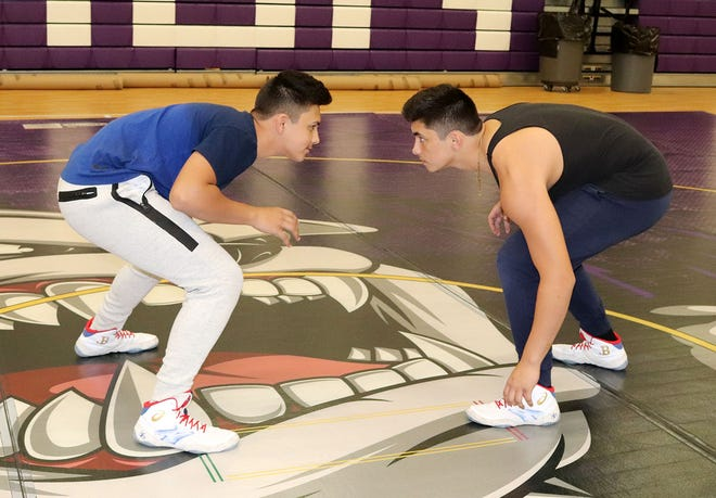Monty Tech freshman Xaedyn Natal, left, gets ready to work on wrestling moves against teammate and older brother, Xavian Natal, during a recent Bulldogs wrestling practice in Fitchburg. Xavian Natal, who wrestles at 170 pounds, is a junior.