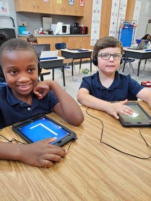 Tyson Chatman and Gavin Thomas use grant-funded iPad Minis in the classroom.