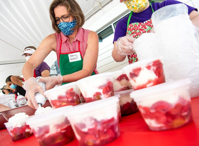 As she prepares to-go orders Thursday, volunteer Nancy Voskuil puts on the whipped cream at the 2021 Strawberry Shortcake Festival at Switchyard Park. The Boys and Girls Clubs of Bloomington Auxiliary's event raises funds for the clubs.