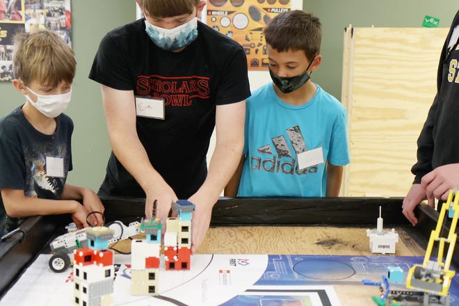 Erik Kaufman, a first-year Team 935 member, helps campers build and program a robot out of Legos during the RaileRobotics Lego Camp this week.