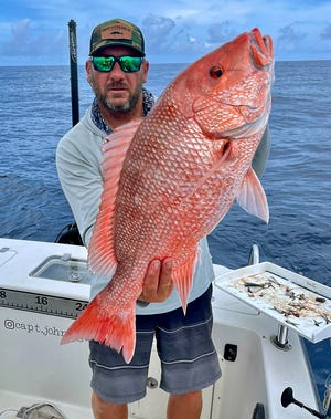Capt. John Gunter of Palmetto shows off a 30-inch American red snapper he caught on a scaled sardine while fishing in 140 feet of water off Anna Maria Island this week.