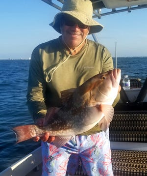 Rex Harris of Winter Haven shows off a keeper 23-inch red grouper he caught on a jig and curly tail plastic swim bait while trolling along the shipping channel in lower Tampa Bay last week.