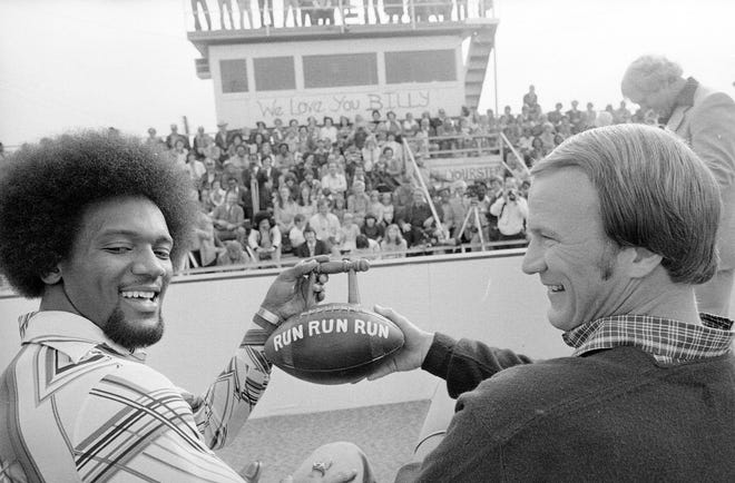Heisman winner Billy Sims, left, and Oklahoma head coach Barry Switzer display a football with a handle, presented to Sims at his alma mater, in Hooks, Texas, on December, 2, 1978. (AP Photo)