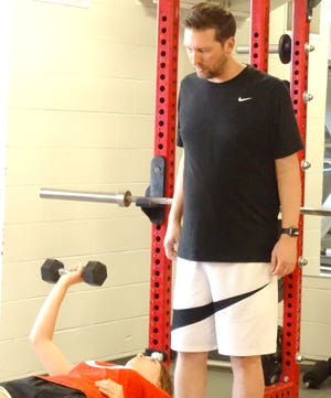 Ottawa High School girls basketball coach Matt Schurman provides encouragement and tips to the Cyclone athletes during their summer lifting sessions.
