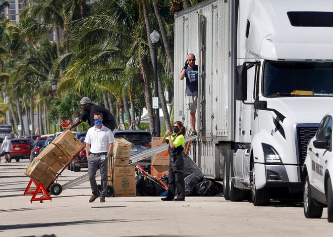 A parking enforcement officer from the town talks with delivery workers as they unload goods from a large truck on Brazilian Ave., October 27, 2020. (DAMON HIGGINS / THE PALM BEACH DAILY NEWS)