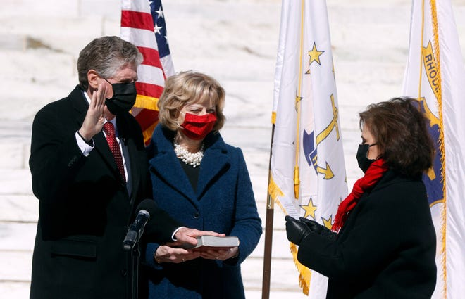 Dan McKee is sworn in as governor by Rhode Island Secretary of State Nellie Gorbea on March 7 as First Lady Susan McKee holds the Bible. He marked his first 100 days in office Thursday.