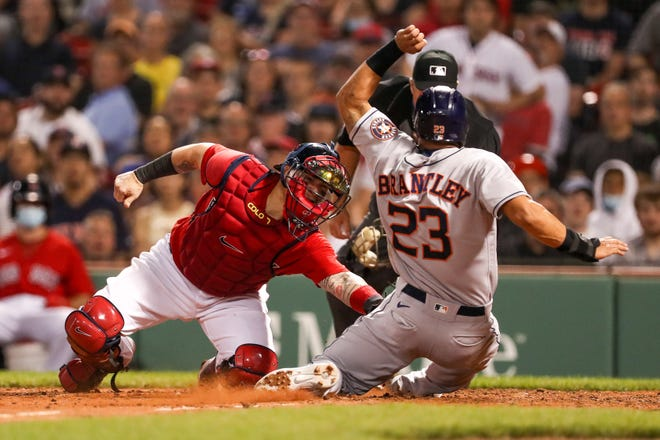 Astros left fielder Michael Brantley (23) slides safely under the tag by Red Sox catcher Christian Vazquez during the seventh inning of Wednesday's game at Fenway Park.