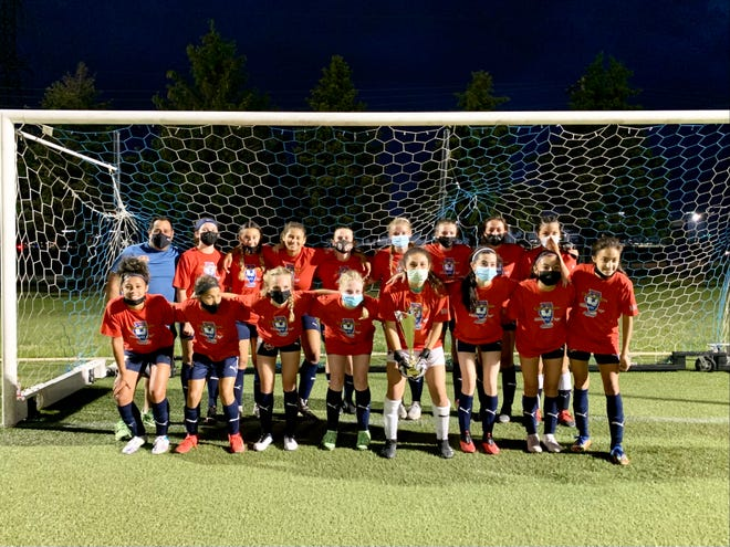 Members of the Rockford Raptors U-15 girls soccer team gather around the Illinois Cup trophy after winning the tourney title on Wednesday, June 9, 2021, at Sportscore Two in Loves Park.