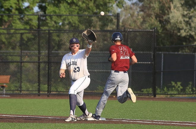 Salina Falcons first baseman Parker Benoit (23) stretches for the ball while the Topeka Scrappers' Scout Jellison (32) reaches base safely during Wednesday's game at Dean Evans Stadium.
