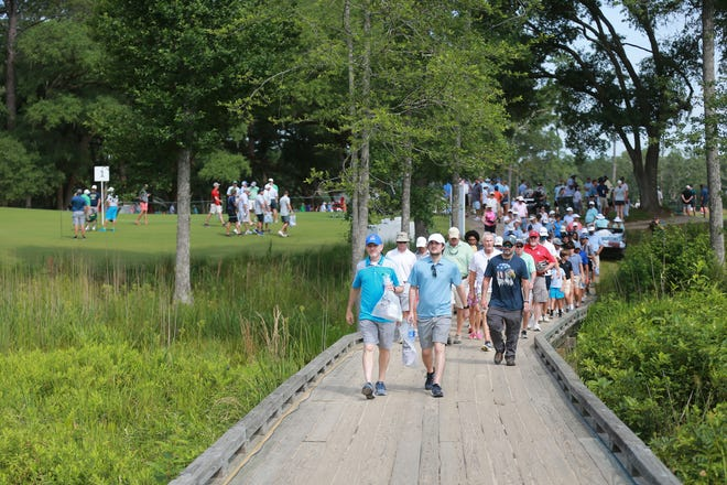 Golf fans cross a bridge on the second hole during the first round of the Palmetto Championship at Congaree on Thursday at Congaree Golf Club.