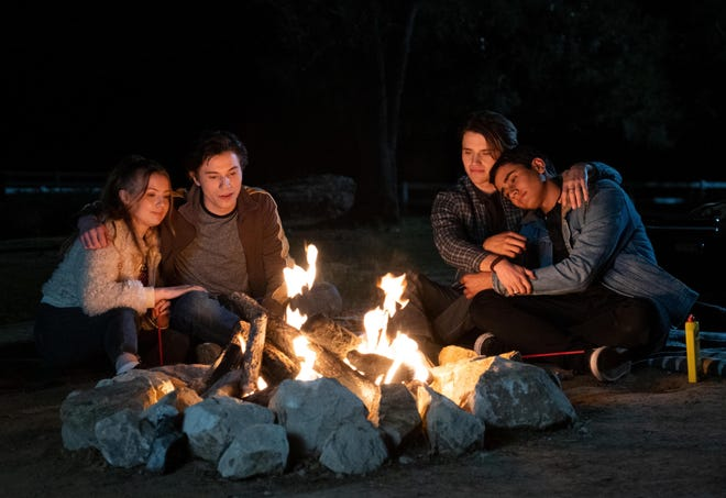 """Bebe Wood (from left), Anthony Turpel, George Sear and Michael Cimino crowd around a fire to mark the end of summer vacation in the season premiere of Hulu's """"Love, Victor,"""" now streaming on Hulu."""