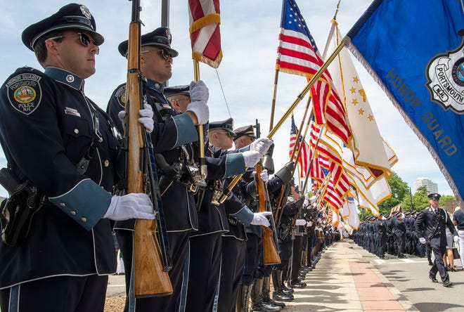 Police department honor guards from across New England line Temple Street after the funeral Mass at St. John Church Thursday.