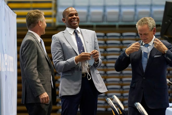 UNC head coach Hubert Davis, center, laughs with chancellor Kevin Guskiewicz, left, and athletic director Bubba Cunningham, right, following a news conference in the Smith Center. Davis was named the Tar Heels' new men's basketball coach on April 6 following the retirement of Roy Williams.