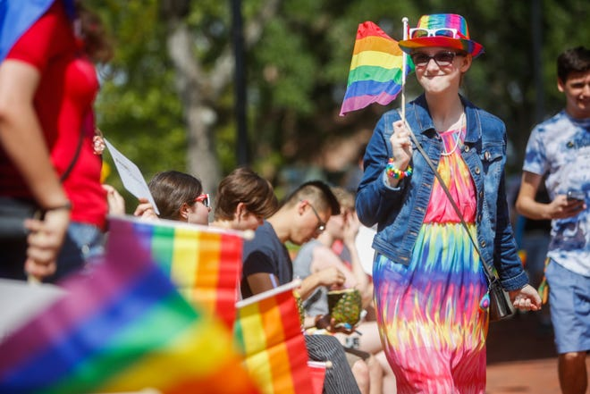 Pride Day participants hold rainbow flags in Gainesville's Bo Diddley Plaza in 2019.