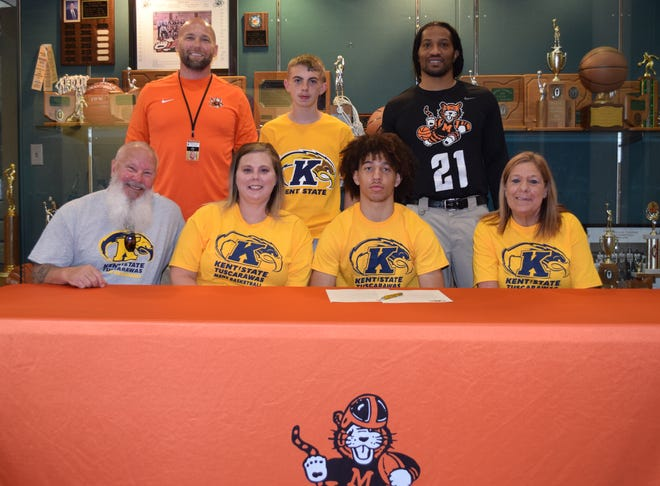 Signing a letter of intent is Cam Burgi(second from right) sitting between his grandfather Al Burgi (left), his mother Michelle Bower, and his grandmother Barbara Burgi. In the back row are Josh Hose, Massillon Head Basketball Coach, Kevin Bower (Cam's stepbrother) and Jamaal Ballard (Cam's stepfather).