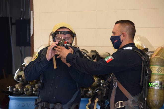 Chihuahua firefighter Pedro M. Alire G. (right) assists Jose O. Acosta D. (left) to secure the face piece of a self-contained breathing apparatus system.