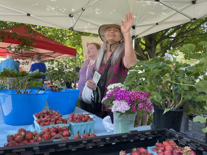 Seejan Black waves to a customer at the Canal Winchester Farmers Market on June 5. Her business, Black Thai Farm, sells locally grown vegetables and flowers and is one of the market's longest-running booths.