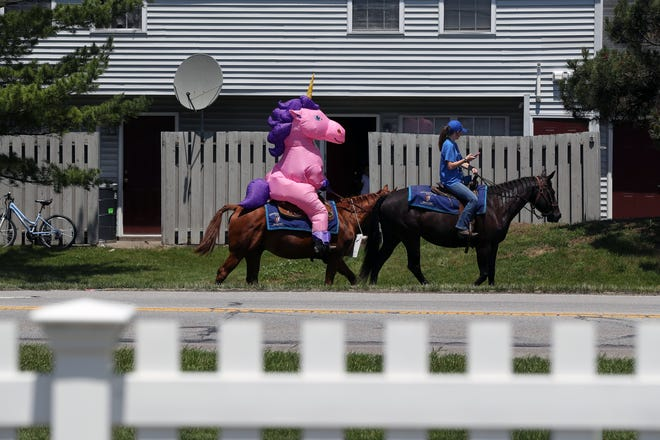 """Chelsey Bush, the owner of Horse-N-Round Fun LLC dressed as a majestic unicorn, and employee Ashley Fielding, 16, ride down Renner Road in Columbus advertising their business June 5. Bush said she is a proponent of """"city riding."""" Her Mount Sterling-based business offers a myriad of activities, including pony parties, petting zoos, horseback trail riding and carriage rides; it also holds themed, public events at Kuhlwein's Farm Market & Deli in Brown Township on the western edge of Hilliard."""