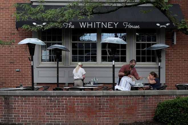 Server Frank Barton brings fresh water out to Eliza Berts and Kimberly Gibson, both of Clintonville, on June 9 at the Whitney House in Worthington. The restaurant is part of the Designated Outdoor Refreshment Area, for which Worthington City Council has expanded hours and days in effect.