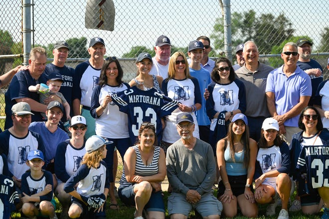 Family and friends of the Martorana family pose for a photo after a ceremony to honor former baseball player Jimmy Martorana before the start of the Medford versus Somerville baseball game at Playstead Park on Wednesday, June 9, 2021.
