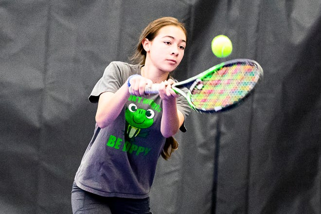Freshman Bella Flores returns a ball during a warmup tennis match at the Cavalier Athletic Center.