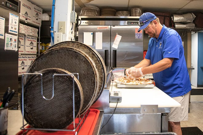 Troy Evans puts the toppings on top of the cheese as he prepares his famous, award-winning Oink Oink Pizza in Kingston, Ohio.