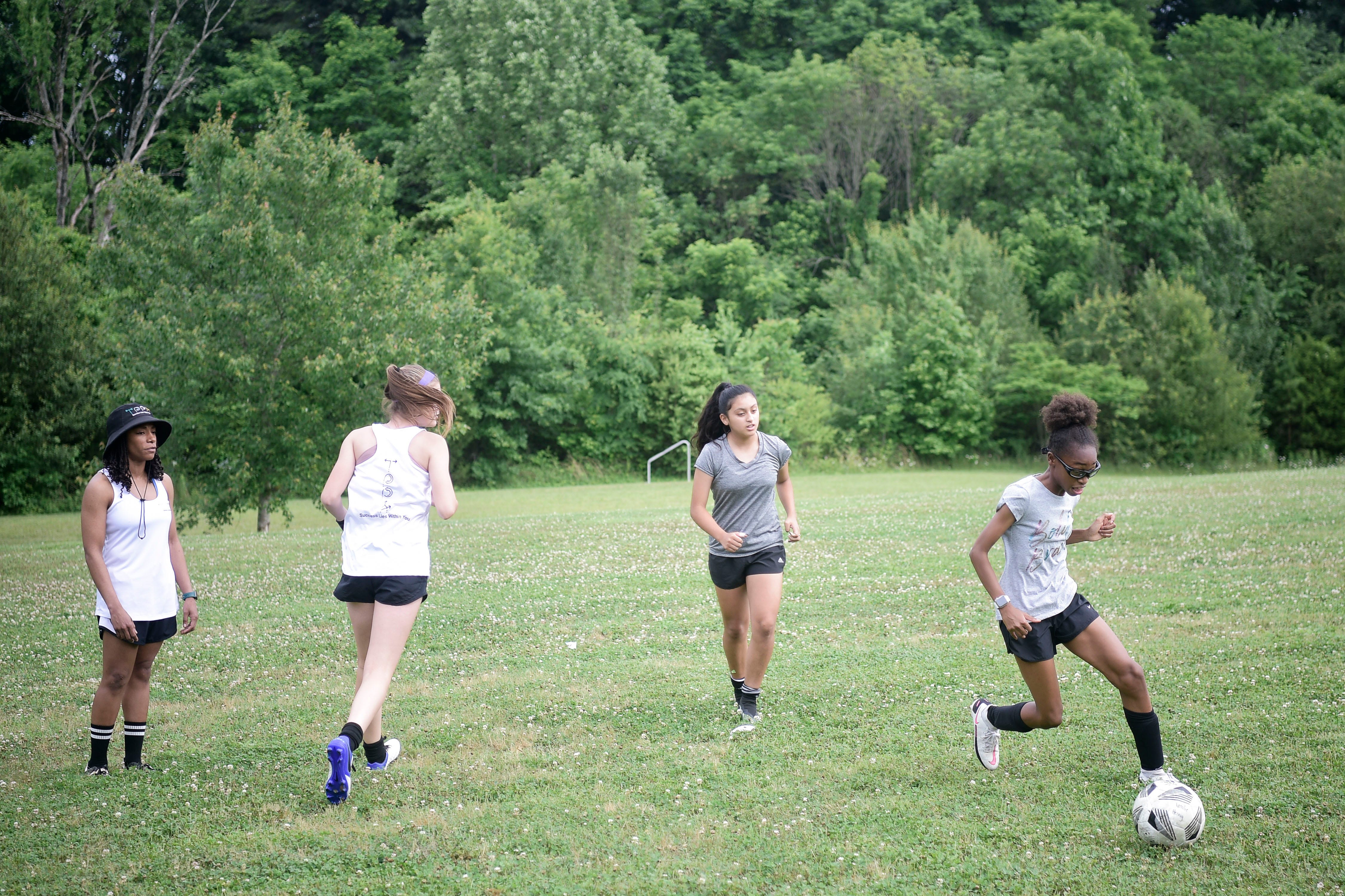 Madison Davis (far right) is not just learning how to play the game through Barrett; she is learning how to become a better teammate, her father said.