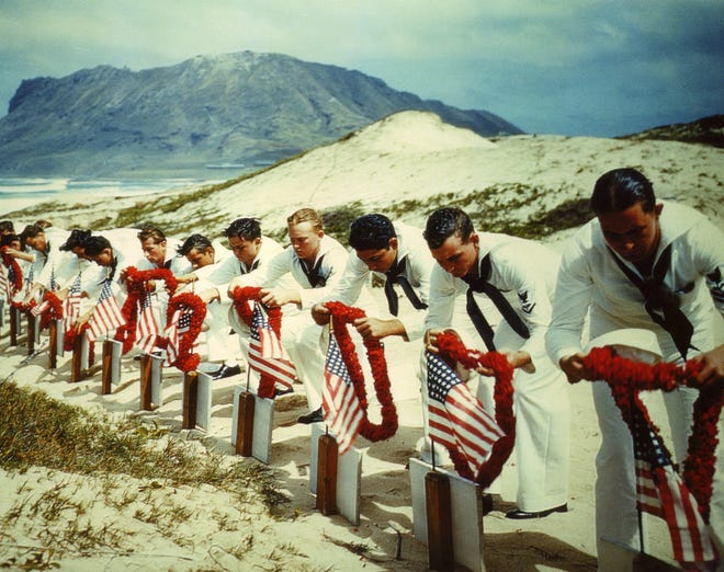 Soldiers place leis and U.S. flags on the graves of 15 servicemen buried near Kaneohe Bay Naval Air Station.