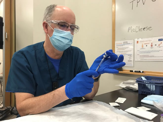 Dan Sheridan prepares a syringe of the Pfizer COVID-19 vaccine at a vaccination clinic in Marion, Ohio in January 2021.