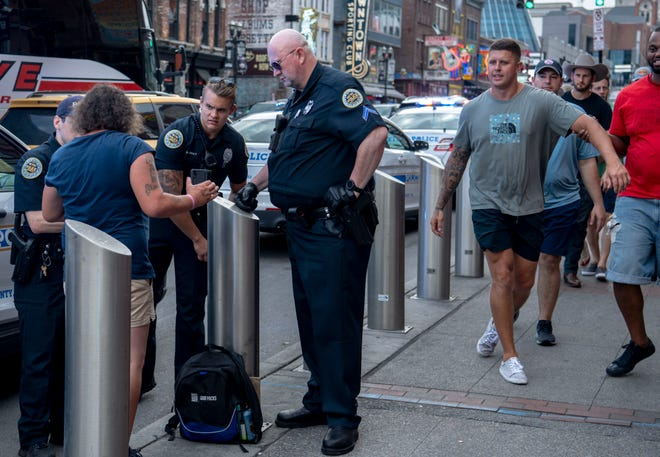 Metro Nashville Police officers talk to a person as they respond to a call on Lower Broadway Thursday, June 10, 2021 in Nashville, Tenn.