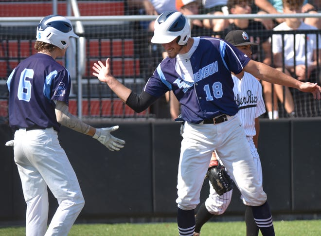 Spartan Aidan Arbogast celebrates with a teammate after scoring Livonia Stevenson's only run of the game.