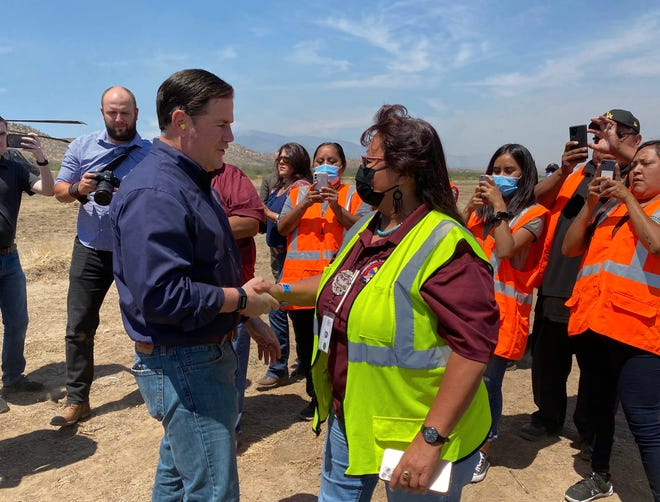 Arizona Gov. Doug Ducey greets aid volunteers and others impacted by the Telegraph and Mescal fires, which have burned more than 150,000 acres in Pinal and Gila counties, on June 10, 2021.