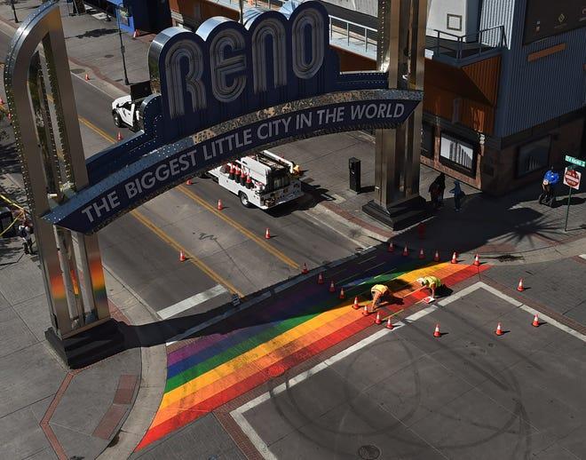 City worker repaint the Pride crosswalk under the Reno Arch on June 9, 2021.
