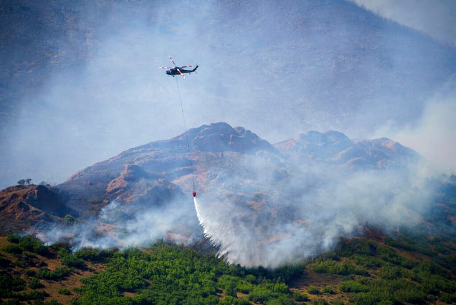 A helicopter makes a drop on the East Canyon Fire as it burns north of East Canyon State Park, on Tuesday, June 8, 2021, near Morgan, Utah. (Chris Samuels/The Salt Lake Tribune via AP)