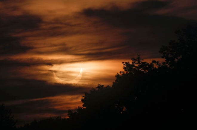 Alors que le soleil se lève dans les Berkshires, la lune passe entre la terre et le soleil, projetant son ombre sur l'hémisphère nord de la terre pour une éclipse solaire annulaire le jeudi 10 juin 2021.