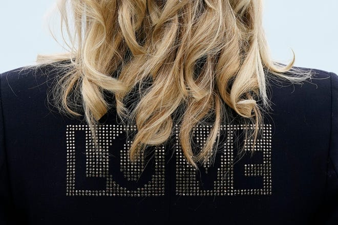 """First lady Jill Biden turns around to show the word """"LOVE"""" on the back of her jacket as she speaks with reporters after visiting with Carrie Johnson, wife of British Prime Minister Boris Johnson, ahead of the G7 summit, June 10, 2021, in Carbis Bay, England."""