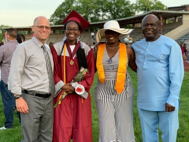 Verda Tetteh with her family and school staff member.