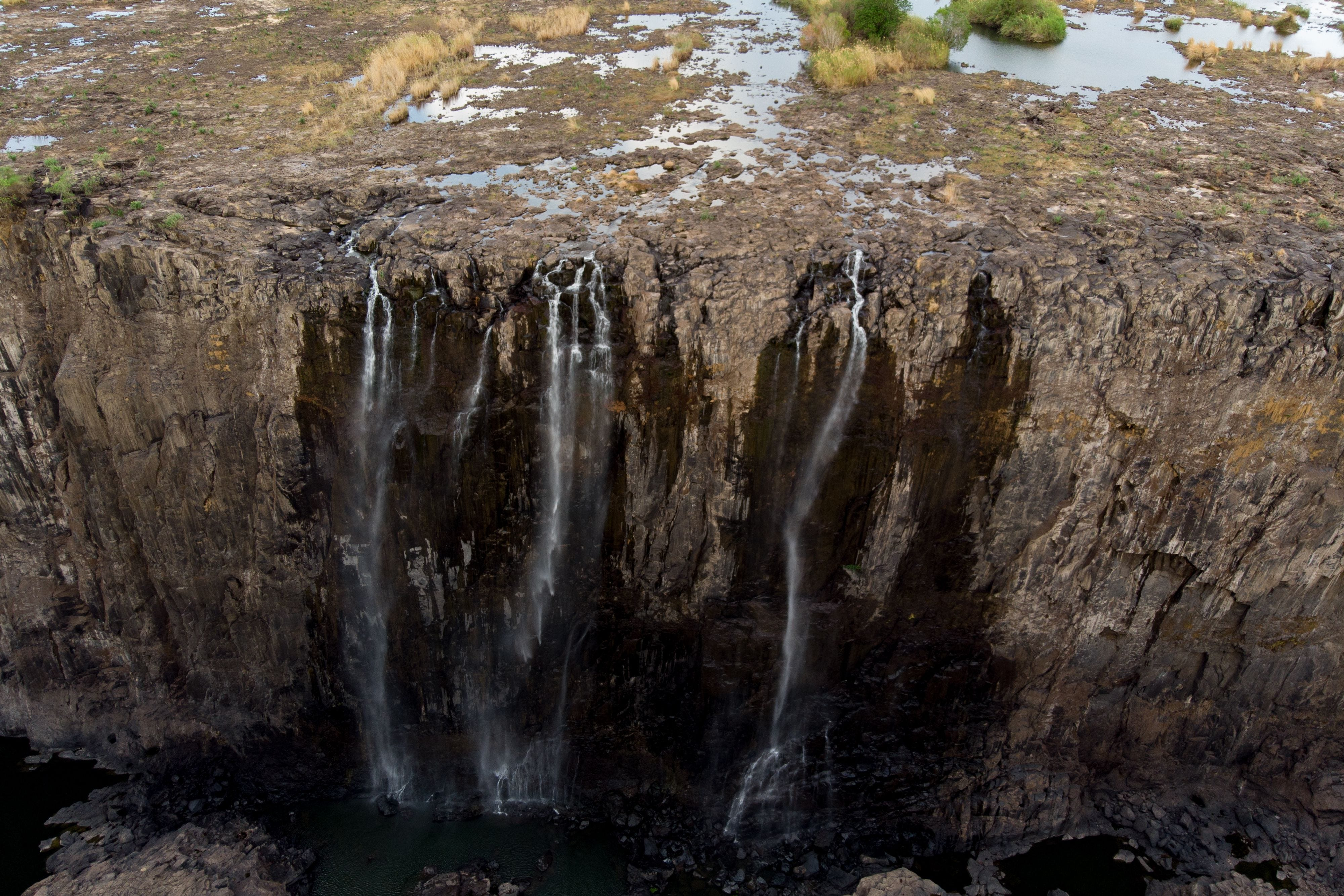A general view of Victoria Falls, in Zimbabwe, on December 10, 2019. The Victoria Falls, a UNESCO world heritage site measuring 108 metres high and almost 2km wide has recorded the lowest levels in recent times due to a severe drought.  Water levels have improved in the past week following rains in the upper Zambezi river yet it is still lower than what it normally carries during this season.