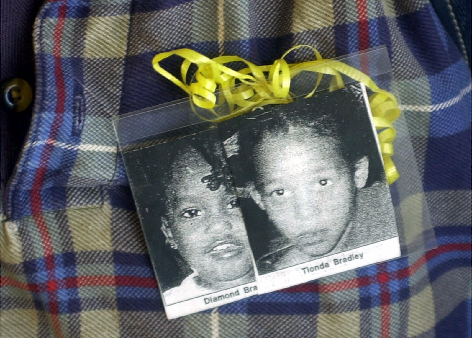 A security guard at Doolittle West Elementary school wears a badge with yellow ribbon holding pictures of missing sisters Diamond and Tionda Bradley Wednesday, July 11, 2001, in Chicago. Neighbors blanketed the area with leaflets and police searched far and wide for the girls.