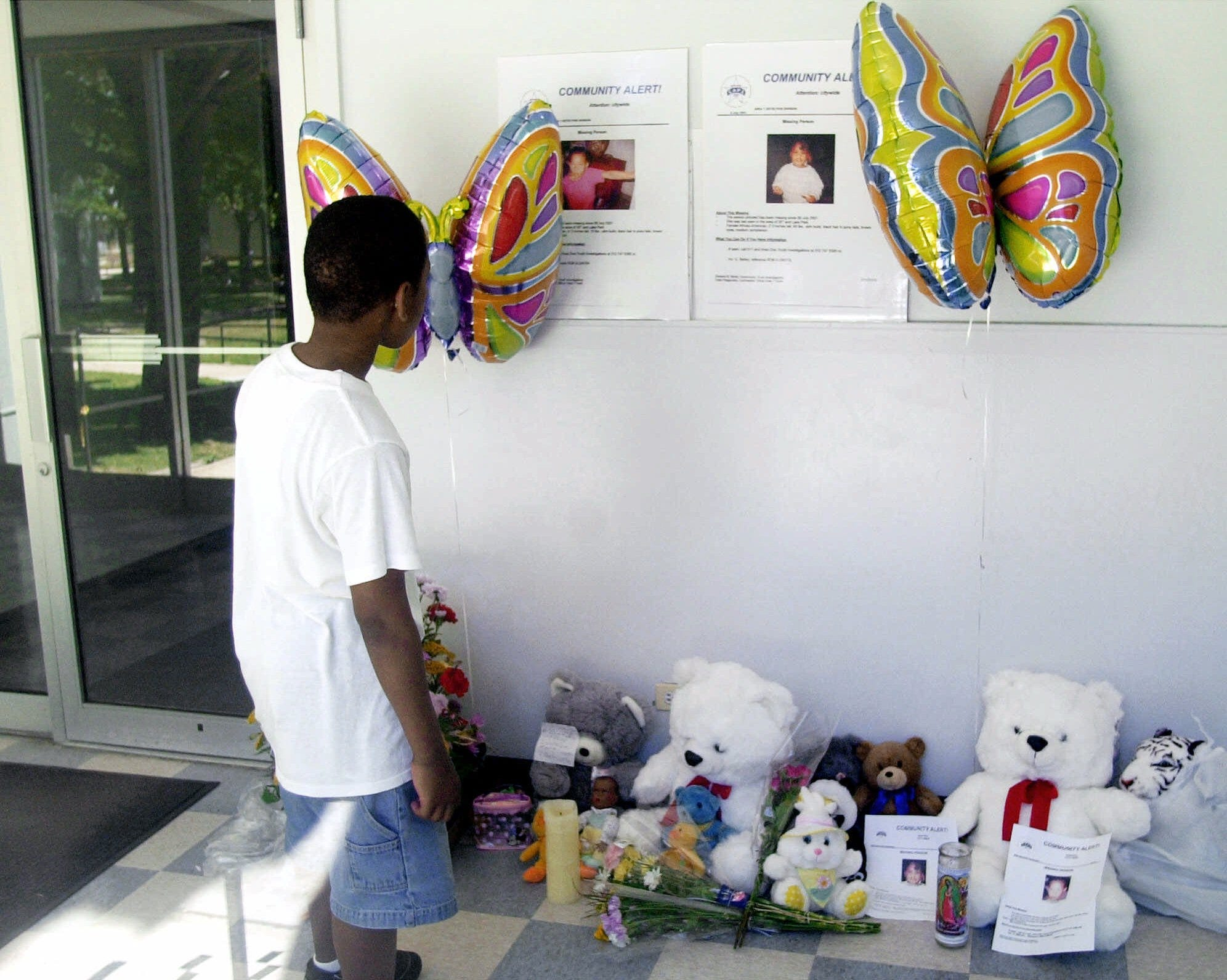 Quamine McClaie, 11, looks at posters of missing sisters Tionda Bradley, 10, and Diamond, left, 3, posted in the lobby of the girls apartment building in Chicago Wednesday, July 11, 2001.
